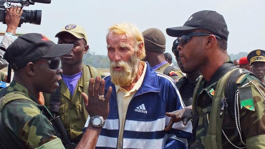 German citizen Robert Nitsch Eberhard, center, as he arrives at the Yaounde Nsimalen International airport, after he was abducted and held hostage by suspected  Boko Haram militants in Yaounde, Cameroon, Wednesday, Jan. 21, 2015. A German man who was kidnapped by the Boko Haram Islamic extremist group in July and freed said Wednesday he never knew if he would survive the ordeal. Looking haggard and with a long blond-gray beard and wearing a blue-and-white Adidas track jacket, Robert Nitsch Eberhard was flown to Yaounde, Cameroon's capital, from Maroua in northern Cameroon in a military flight. (AP Photo/Moki Edwin Kindzeka)