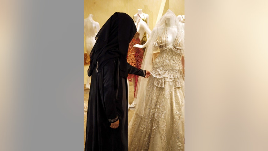 "FILE - In this Aug. 3, 2008 file photo, a Saudi woman checks a wedding dress at a shop in Riyadh, Saudi Arabia. Under Saudi Arabia's Wahhabi interpretation of Islam, the sexes are strictly segregated, making it harder for young people to meet. Morality police keep women and men apart in restaurants, malls and public spaces, and schools and most universities are segregated. The increase in single women has alarmed the country's clerics, who have responded by pushing for early marriage and preaching on the evil consequences of ""spinsterhood,"" such as sex outside wedlock. (AP Photo, File)"