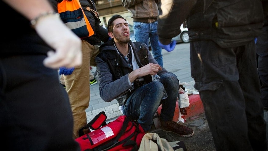 "An injured man sits as he is treated by paramedics at the scene of a stabbing in Tel Aviv, Israel, Wednesday, Jan. 21, 2015. A Palestinian man stabbed nine people, injuring several seriously, on a bus in central Tel Aviv before he was chased down, shot and arrested, Israeli police said Wednesday, describing the assault as a ""terror attack"" in the latest in a spate of violence, the worst Israel has seen in almost a decade. (AP Photo/Oded Balilty)"