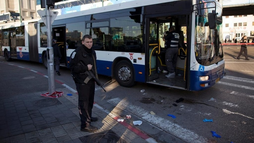 An Israeli police officer secures the scene after a stabbing in Tel Aviv, Israel, Wednesday, Jan. 21, 2015. A Palestinian man stabbed nine people, injuring several seriously, on a bus in central Tel Aviv before he was chased down, shot and arrested, Israeli police said Wednesday. (AP Photo/Oded Balilty)