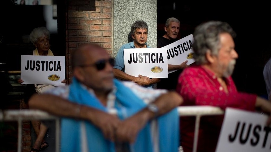 "People gather outside the AMIA Jewish community center asking for ""Justice"" in the death of a  prosecutor who had accused Argentina's president of a criminal conspiracy, in Buenos Aires, Argentina, Wednesday, Jan. 21, 2015. Special prosecutor Alberto Nisman, who had been investigating the 1994 bombing of the Jewish community center that killed 85 people and who accused President Cristina Fernandez of shielding Iranian suspects, was found dead from a gunshot to the head, in his apartment late Sunday, hours before he was to testify in a Congressional hearing about the case. (AP Photo/Rodrigo Abd)"