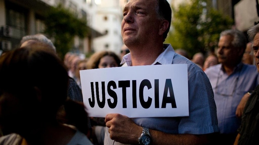 "A man holds a sign that reads in Spanish; 'Justice' outside the AMIA Jewish community center, where a group gathered asking for ""Justice"" in the death of a  prosecutor who had accused Argentina's president of a criminal conspiracy, in Buenos Aires, Argentina, Wednesday, Jan. 21, 2015. Special prosecutor Alberto Nisman, who had been investigating the 1994 bombing of the Jewish community center that killed 85 people and who accused President Cristina Fernandez of shielding Iranian suspects, was found dead from a gunshot to the head, in his apartment late Sunday, hours before he was to testify in a Congressional hearing about the case. (AP Photo/Rodrigo Abd)"