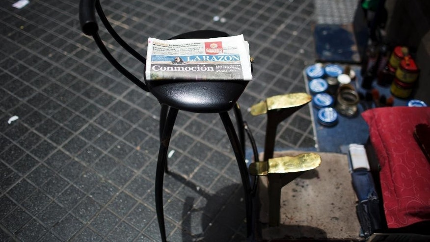 "A newspaper whose cover reads ""Commotion"", referring to the death of special prosecutor Alberto Nisman, sits on a shoeshine stand in  Buenos Aires, Argentina, Tuesday, Jan. 20, 2015. Nisman, who had been investigating the 1994 bombing of the AMIA Jewish community center in Buenos Aires that killed 85 people and who accused President Cristina Fernandez of shielding Iranian suspects, was found dead from a gunshot to the head, in his apartment late Sunday, hours before he was to testify in a Congressional hearing about the case. (AP Photo/Rodrigo Abd)"
