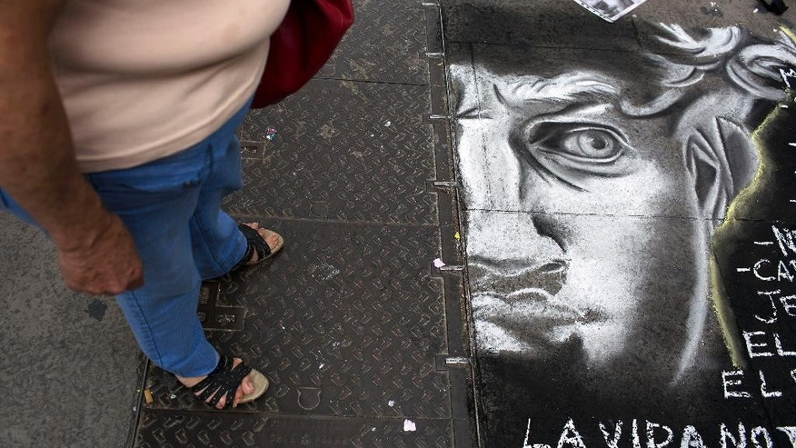 A woman looks at a drawing depicting the figure of the justice, on a sidewalk in Buenos Aires, Argentina, Tuesday, Jan. 20, 2015. Special prosecutor Alberto Nisman, who had been investigating the 1994 bombing of the AMIA Jewish community center in Buenos Aires that killed 85 people and who accused President Cristina Fernandez of shielding Iranian suspects, was found dead from a gunshot to the head, in his apartment late Sunday, hours before he was to testify in a Congressional hearing about the case. (AP Photo/Rodrigo Abd)