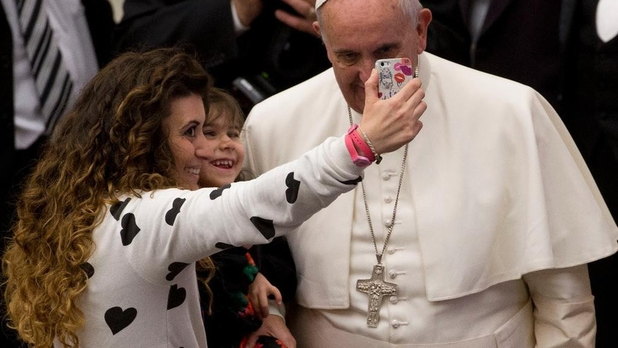 "A woman and a child take a selfie photo with Pope Francis, right, during his weekly general audience in the Paul VI hall at the Vatican, Wednesday, Jan. 21, 2015. Pope Francis is praising big families after saying Catholics don't have to breed ""like rabbits."" He says big families are a gift and don't cause poverty in the developing world, and that the real cause of poverty is an unjust economic system that idolizes money over people. (AP Photo/Andrew Medichini)"