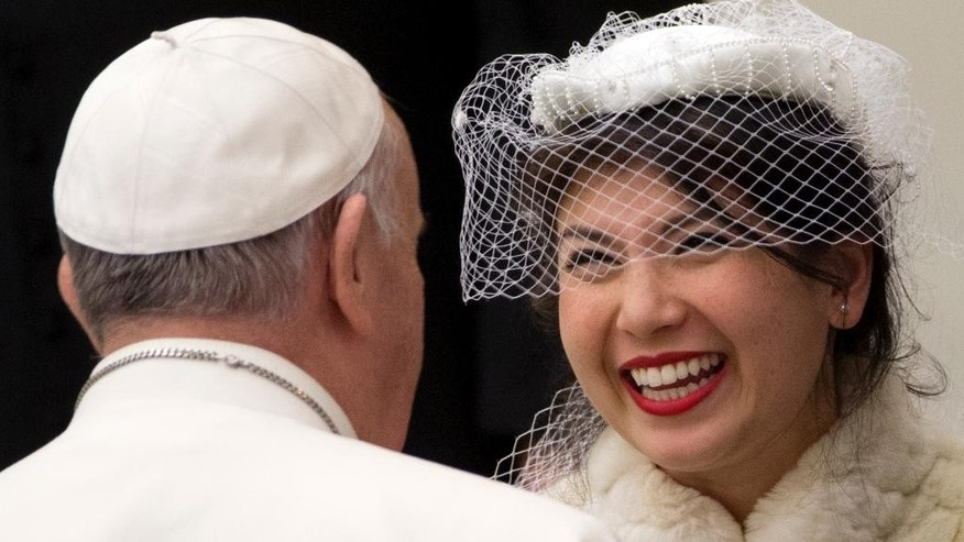 "A bride, right, smiles at Pope Francis as he meets newly wed couples during his weekly general audience in the Paul VI hall at the Vatican, Wednesday, Jan. 21, 2015. The pontiff is praising big families after saying Catholics don't have to breed ""like rabbits."" He says big families are a gift and don't cause poverty in the developing world, and that the real cause of poverty is an unjust economic system that idolizes money over people. (AP Photo/Andrew Medichini)"