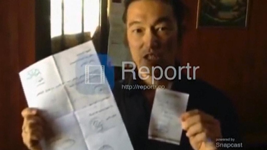 In this still image from an Oct. 2, 2014 Reportr video released by Independent Press and Pacific Bridge Media & Consulting, Japanese video journalist Kenji Goto holds up his entry pass to Syria while reporting from an unknown location near the border. The Islamic State group released a video on Tuesday, Jan. 20, 2015, threatening to kill two Japanese hostages, Goto, 47, and Haruna Yukawa, 42, within 72 hours unless it receives $200 million. (AP Photo/Reportr by Independent Press and Pacific Bridge Media & Consulting)
