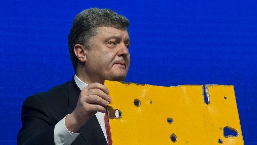 "Ukrainian President Petro Poroshenko shows a piece of a bus that was attacked recently during the panel ""The Future of Ukraine"" in Davos, Switzerland, Wednesday, Jan. 21, 2015. The meeting runs Jan. 21 through 24 under the overarching theme ""The New Global Context"". (AP Photo/Michel Euler)"