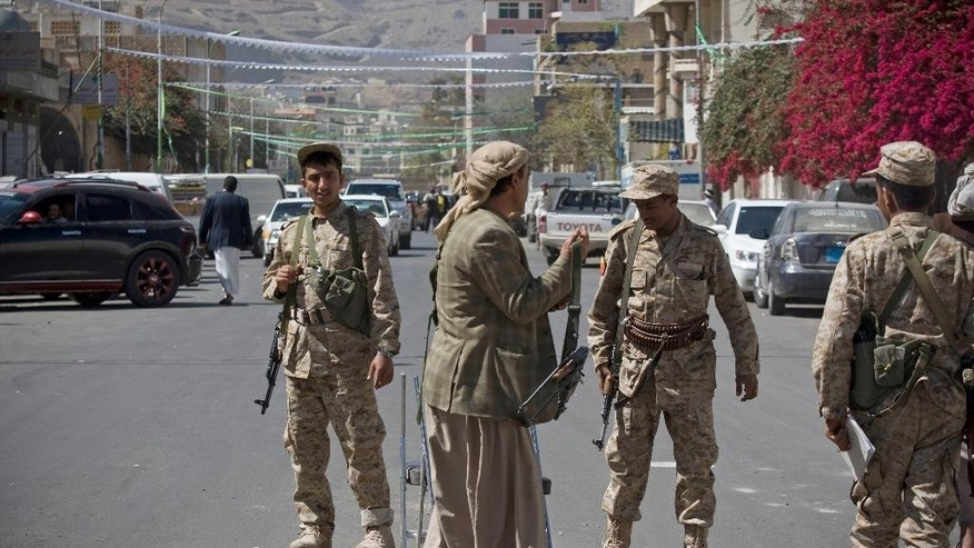 Houthi Shiite Yemeni wearing army uniforms stand guard on a street leading to the presidential palace in Sanaa, Yemen, Wednesday, Jan. 21, 2015. Authorities in southern Yemen have closed the country's second-largest airport there in protest over the Shiite rebels' power grab in the capital, Sanaa, which has plunged the nation deeper into chaos and threatens to fracture the country. (AP Photo/Hani Mohammed)