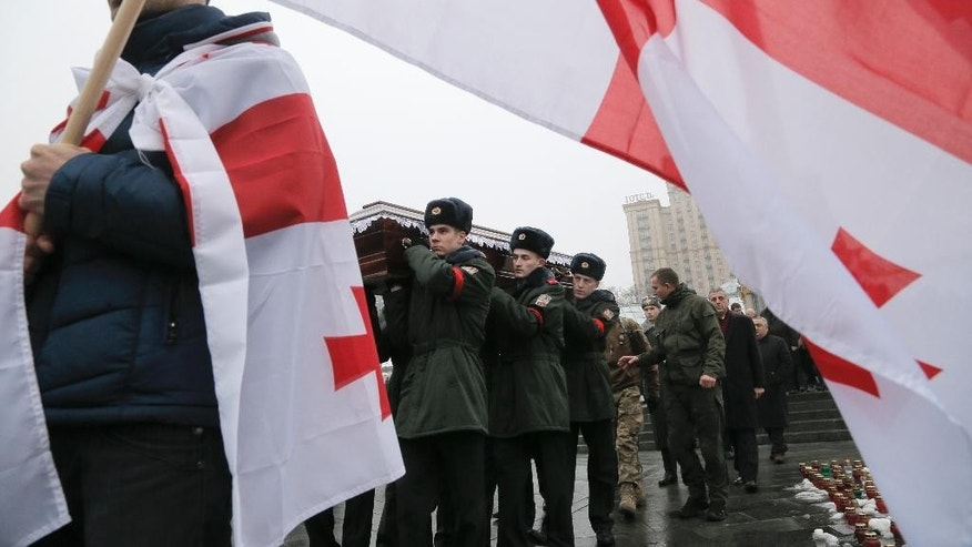 A man carries a Georgian flag as Ukrainian soldiers carry the coffin bearing the body of serviceman Thomas Sukhiashvili, a Georgian national who was killed in fighting against Russian-backed separatists, during a commemoration ceremony in Kiev, Ukraine, on Wednesday, January 21, 2015. Sukhiashvil was a veteran of NATO-led campaigns in Afghanistan and Iraq and Georgia's 2008 war with Russia.  A former senior Georgian military official says around 100 Georgian volunteers are fighting alongside Ukrainian forces in the conflict against Russian-backed separatists.(AP Photo/Efrem Lukatsky)