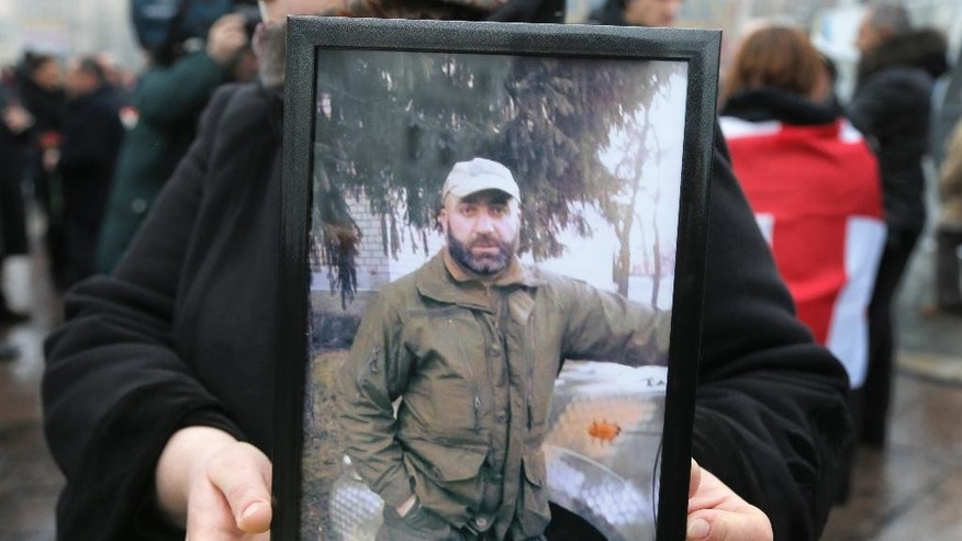 A woman holds a photo of Thomas Sukhiashvili, a Georgian national who was killed in fighting against Russian-backed separatists, during a commemoration ceremony in Kiev, Ukraine, on Wednesday, January 21, 2015. Sukhiashvil was a veteran of NATO-led campaigns in Afghanistan and Iraq and Georgia's 2008 war with Russia.  A former senior Georgian military official says around 100 Georgian volunteers are fighting alongside Ukrainian forces in the conflict against Russian-backed separatists.(AP Photo/Efrem Lukatsky)
