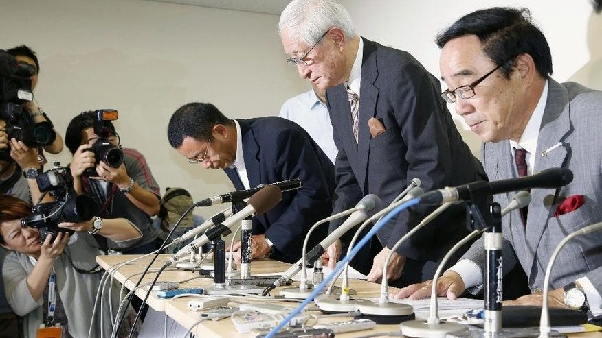 FILE - This June 14, 2013, file photo shows Nippon Professional Baseball commissioner Ryozo Kato, center, bowing to the media after attending a news conference following a meeting with representatives of the 12 teams in Tokyo. Kato apologized for the confusion caused by introducing a new, livelier ball this season without notifying players. Scuffed balls, scratched balls, balls switched mid-game. Suspected ball-doctoring isn't only an issue for the NFL, which is investigating a report that the New England Patriots used underinflated footballs in the AFC championship game while beating the Indianapolis Colts 45-7. (AP Photo/Kyodo News, File) JAPAN OUT, MANDATORY CREDIT