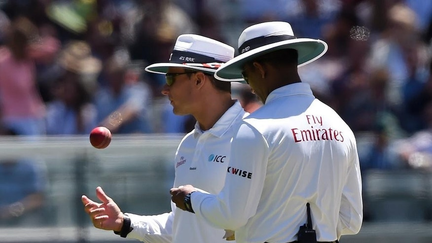 FILE - In this Dec. 27, 2014, file photo, umpire Richard Kettleborough of England, left, tosses the ball up as he and fellow umpire, Sri Lanka's Kumar Dharmasena, wait for a replacement ball during play on day two of the cricket test match between India and Australia in Melbourne, Australia. Scuffed balls, scratched balls, balls switched mid-game. Suspected ball-doctoring isn't only an issue for the NFL, which is investigating a report that the New England Patriots used underinflated footballs in the AFC championship game while beating the Indianapolis Colts 45-7. (AP Photo/Andy Brownbill, File)