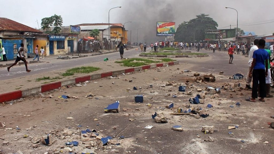 Rocks are seen in a main street as anti government protestors burn tires during a protest against a new law that could delay election to be held in 2016, in the city of Kinshasa, Democratic Republic of Congo, Monday, Jan. 19, 2015, The revised election law will require  a national census be carried out before elections can be held in 2016, that could have the effect that President Joseph Kabila remains in power after his mandate expires in 2016. (AP Photo/John Bompengo)