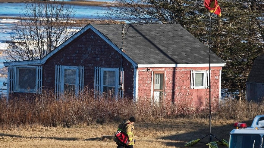 A firefighter crosses the lawn where a large quantity of unidentified chemicals were found in a residence in Grand Desert, Nova Scotia, Wednesday, Jan. 21, 2015. A 42-year-old man, who was the subject of a Canada-wide warrant following an overnight investigation linked to the evacuation of two areas in Halifax where police found a large quantity of chemicals they have yet to identify, was taken into custody. (AP Photo/The Canadian Press, Andrew Vaughan)