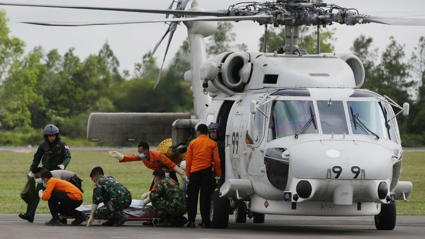 Jan. 9, 2015: Members of Japan Maritime Self-Defense Force and Indonesian Search and Rescue Agency unload the body of a victim aboard AirAsia Flight 8501 from a helicopter upon arrival at the airport in Pangkalan Bun, Indonesia.