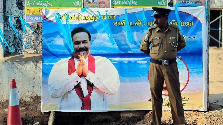 FILE - In this Friday, Jan. 2, 2015 file photo, a Sri Lankan police officer stands by a banner of President Mahinda Rajapaksa outside an election campaign venue in Mannar, an area with majority Tamil inhabitants, Sri Lanka. Their friends have deserted them. Their houses have been raided. Their power, near-absolute on this island nation just a month ago, has melted away, replaced with talk that some in the family could face charges of corruption and perhaps even murder. And former President Rajapaksa and his family - the brothers, son, nephews and cousins who have dominated Sri Lanka for nearly a decade - are suddenly portraying themselves as victims. Rajapaksa lost the January 8 presidential election to his former ally Maithripala Sirisena. (AP Photo/Eranga Jayawardena, File)