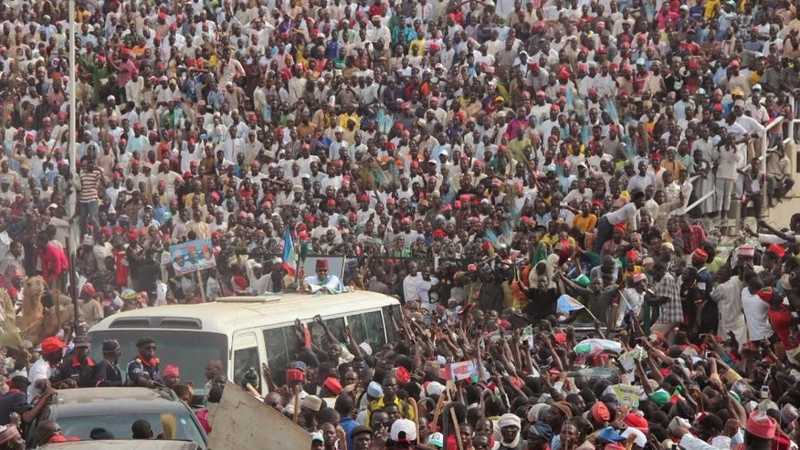 In this photo taken on Tuesday, Jan. 20, 2015, Nigerian presidential candidate Muhammadu Buhari, center, from the All Progressives Congress (APC) rides atop a bus as he arrives during a party rally in Kano, Nigeria. A Dutch lawyer at the ICC and Nigerian rights activists say they have evidence showing Nigeria's 2015 presidential candidate Muhammadu Buhari instigated violence that led to the killings of some 800 people after he lost 2011 elections. (AP Photo/Sani Maikatanga)