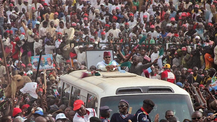 In this photo taken on Tuesday, Jan. 20, 2015, Nigerian presidential candidate Muhammadu Buhari, center, from the  All Progressives Congress (APC) party rides atop a bus as he arrives for a party rally in Kano, Nigeria. A Dutch lawyer at the ICC and Nigerian rights activists say they have evidence showing Nigeria's 2015 presidential candidate Muhammadu Buhari instigated violence that led to the killings of some 800 people after he lost 2011 elections. (AP Photo/Sani Maikatanga)
