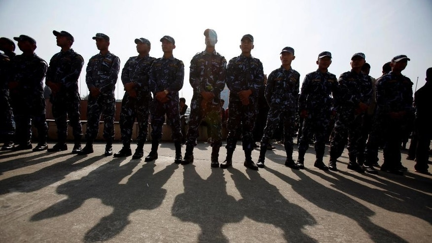 Nepalese security men stand guard outside Constituent Assembly hall in Kathmandu, Thursday, Jan. 22, 2015. Nepal's opposition parties protested both inside parliament and on the streets Thursday against governing coalition plans to push through a draft of a new constitution. (AP Photo/Niranjan Shrestha)