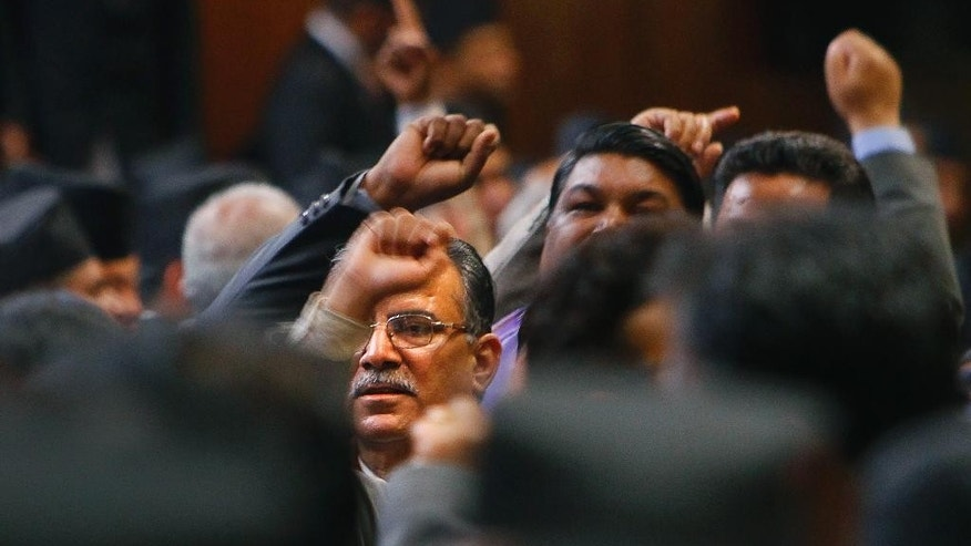 Pushpa Kamal Dahal, center, leader of Unified Communist Party of Nepal, shouts slogans during the process of formation of new draft of constitution in Kathmandu, Thursday, Jan. 22, 2015. Nepal's opposition parties protested both inside parliament and on the streets Thursday against governing coalition plans to push through a draft of a new constitution. (AP Photo/Niranjan Shrestha)