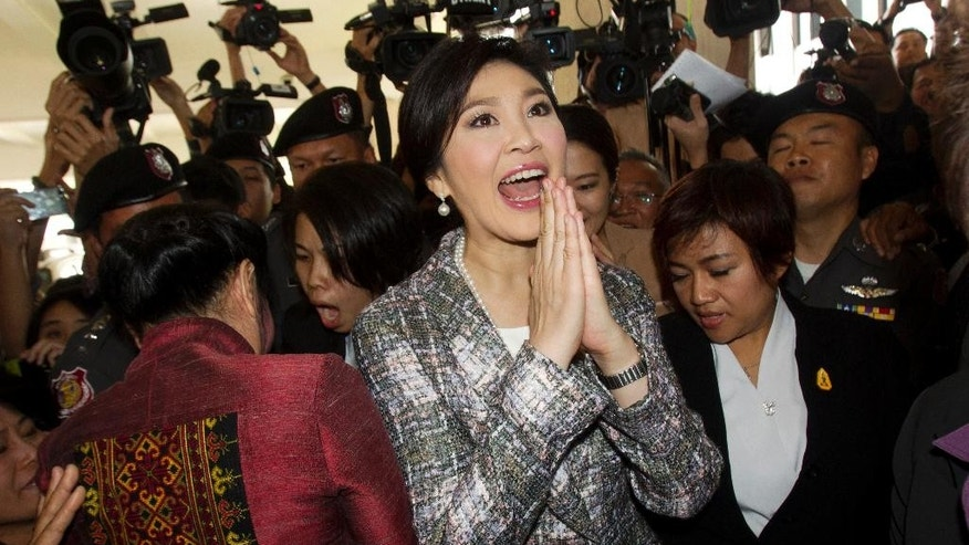 Thailand's former Prime Minister Yingluck Shinawatra, center, leaves parliament in Bangkok, Thailand, Thursday, Jan. 22, 2015. Thailand's military-appointed legislature is set to vote on impeachment against Yingluck over a government's rice subsidy scheme on Friday. (AP Photo/Sakchai Lalit)