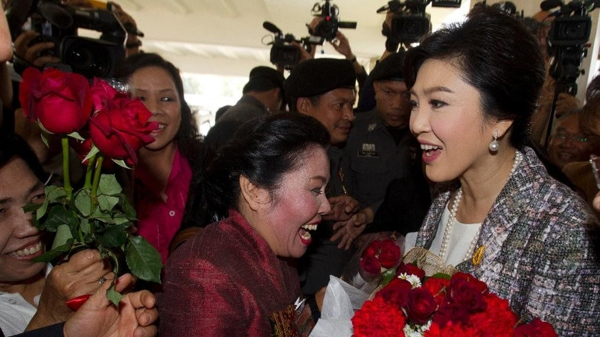 Thailand's former Prime Minister Yingluck Shinawatra, right, receives flowers from her supporters as she leaves parliament in Bangkok, Thailand, Thursday, Jan. 22, 2015. Thailand's military-appointed legislature is set to vote on impeachment against Yingluck over a government's rice subsidy scheme on Friday. AP Photo/Sakchai Lalit)