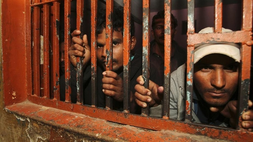 Indian fishermen sit behind bars in Karachi, Pakistan, Thursday, Jan. 22, 2015. A Pakistani police officer said the country's Maritime Security Agency has arrested 38 Indian fishermen for violating its waters in the Arabian Sea. (AP Photo/Fareed Khan)