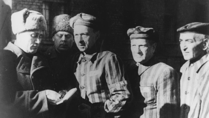 "FILE- In this file photo dated January 1945, three Auschwitz prisoners, right, talk with Soviet soldiers after the Nazi concentration camp Auschwitz, in Poland, was liberated by the Russians.  On Thursday Jan. 22, 2015, Russia accused Poland of engaging in a ""mockery of history"" after the Polish foreign minister Grzegorz Schetyna credited Ukrainian soldiers, rather than the Soviet Red Army, with liberating Auschwitz 70-years ago. The latest exchange comes prior to the 70th anniversary of the liberation of Auschwitz by Soviet troops on Jan. 27, 1945, underlining deep tensions between Russia and Poland, which is hugely critical of Russia's recent actions in Ukraine. (AP Photo/FILE)"