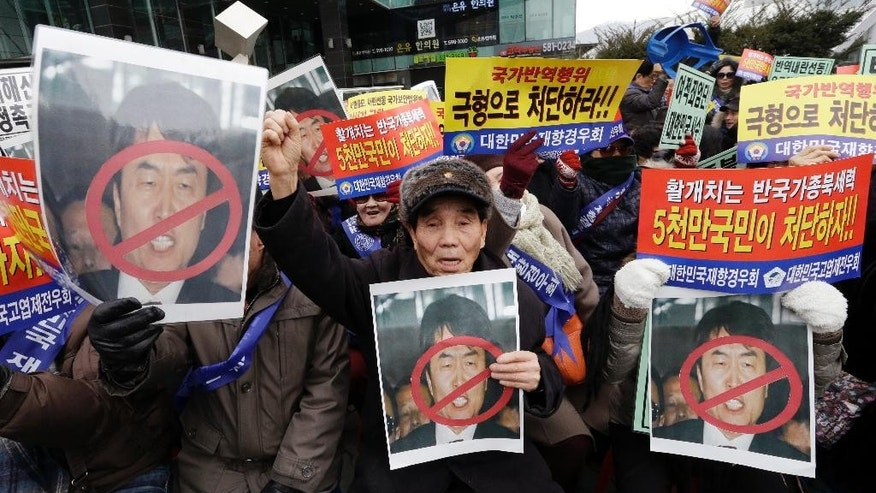 "Members of conservative groups hold defaced portraits of former Unified Progressive Party lawmaker Lee Seok-ki as they shout slogans during a rally denouncing Lee near the Supreme Court in Seoul, South Korea, Thursday, Jan. 22, 2015. South Korea's Supreme Court on Thursday upheld a prison sentence for Lee arrested for encouraging an armed rebellion in the South should war with North Korea break out. The letters on placards read "" Punish Lee Seo-ki."" (AP Photo/Ahn Young-joon)"