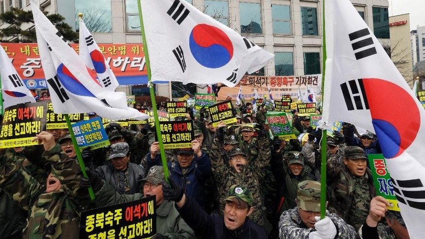 "South Korean Vietnam War veterans with national flags shout slogans during a rally denouncing former Unified Progressive Party lawmaker Lee Seok-ki  near the Supreme Court in Seoul, South Korea, Thursday, Jan. 22, 2015. South Korea's Supreme Court on Thursday upheld a prison sentence for  Lee arrested for encouraging an armed rebellion in the South should war with North Korea break out. The letters on placards read "" Punish Lee Seo-ki."" (AP Photo/Ahn Young-joon)"