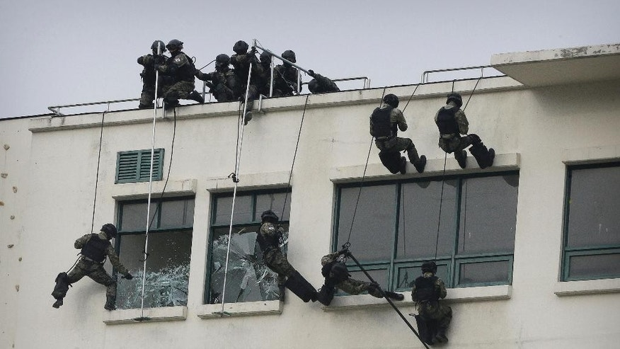 South Korean army soldiers break the window glasses during an exercise against a terrorist attack at a training camp in Seoul, South Korea, Wednesday, Jan. 21, 2015. Seoul Metropolitan Police Agency said that it is a part of preparation to counteract terror since threats of terrorism are growing worldwide. (AP Photo/Ahn Young-joon)