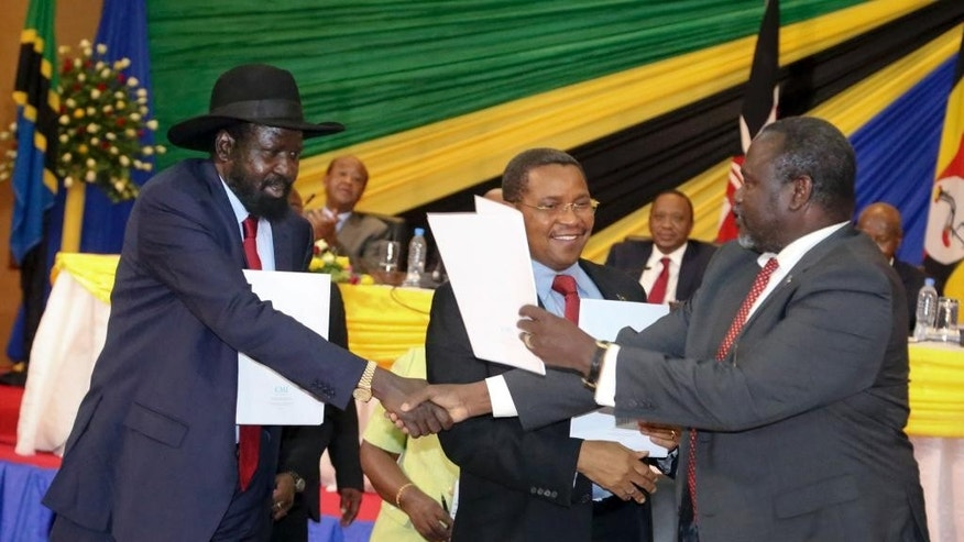 In this photo taken Wednesday, Jan. 21, 2015, South Sudan's President Salva Kiir, left, shakes hands with rebel leader and former vice president Riek Machar, right, as Tanzania's President Jakaya Kikwete, center, looks on after signing an agreement at the end of talks in Arusha, Tanzania.  South Sudan's warring factions have agreed to reunify their political party, a conflict resolution organization said Thursday, with South Sudan President Salva Kiir and rebel leader Riek Machar signing the agreement to unite the ruling Sudan People's Liberation Movement on Wednesday in the Tanzanian town of Arusha, according to the Conflict Management Initiative. (AP Photo)