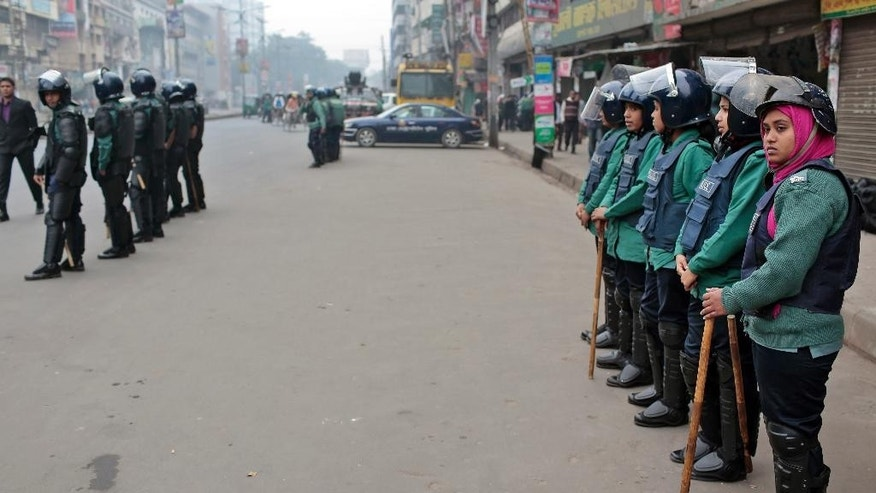In this Jan. 21, 2015 photo, Bangladeshi police stand guard in front of the Bangladesh Nationalist Party (BNP) party office during the nationwide strike called by them in Dhaka, Bangladesh. Since Jan. 5 - the one-year anniversary of the last election - at least 28 people have been killed, nearly 700 vehicles have been smashed or torched and much of the country's transportation system has been at a standstill. Supporters of former Prime Minister Khaleda Zia, who boycotted the last vote, demand that the government resign and hold new elections immediately, but Prime Minister Sheikh Hasina says her government will remain in office until her term ends in 2019. (AP Photo/A.M. Ahad)