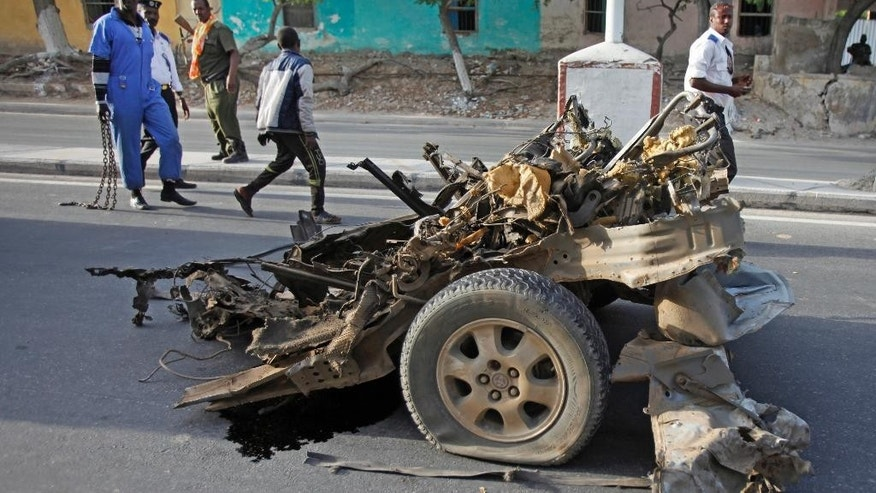 Somalis walk past the wreckage of a car used in a suicide bombing in Mogadishu, Somalia, Thursday, Jan. 22, 2015. A suicide car bomber blew himself up at the gate of the city's SYL hotel which was being used by a delegation of Turkish officials, killing three Somalis and shattering windows, and coming one day before Turkish President Recep Tayyip Erdogan was due to arrive in the Somali capital. (AP Photo/Farah Abdi Warsameh)