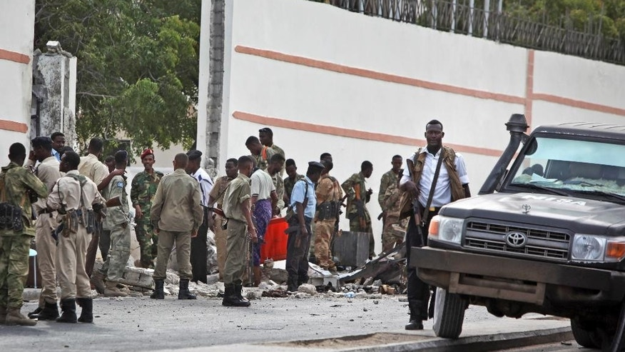 Somali soldiers gather near the destroyed gate of the SYL hotel following a suicide car bomb attack in Mogadishu, Somalia, Thursday, Jan. 22, 2015. A suicide car bomber blew himself up at the gate of the hotel which was being used by a delegation of Turkish officials, killing three Somalis and shattering windows, and coming one day before Turkish President Recep Tayyip Erdogan was due to arrive in the Somali capital. (AP Photo/Farah Abdi Warsameh)