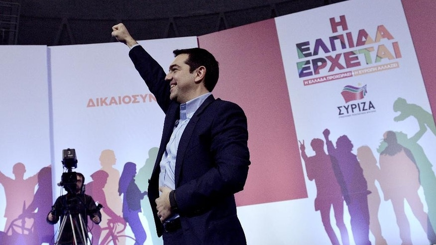 Alexis Tsipras, head of Greece's Syriza leftwing main opposition party waves to his supporters during a pre-election campaign speech, at the Nick Galis Hall, in the northern Greek port city of Thessaloniki on Tuesday, Jan. 20, 2015. Prime Minister Antonis Samaras' New Democracy party has failed so far to overcome a gap in opinion polls with the anti-bailout Syriza party ahead of the Jan. 25 general election. The banner, right, reads ''Hope is on the way.'' (AP Photo/Giannis Papanikos)