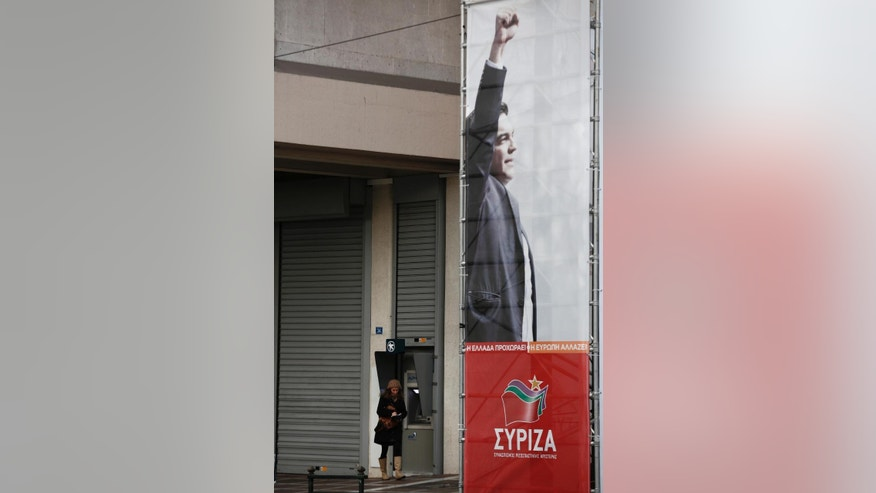 In this Saturday Jan. 17, 2015 photo, a woman uses an ATM behind a pre-election poster of Alexis Tsipras, head of Greece's Syriza left-wing main opposition party, in Athens. His left-wing Syriza party is poised to win a general election in Greece Sunday, a landmark event for Europe's ambitious political newcomers with domestic resonance in a country with a long history of deadly political division that has recently been ravaged by financial crisis. (AP Photo/Yorgos Karahalis)