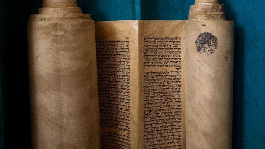 An ancient Torah scroll is seen during a dedication ceremony at the Israeli Foreign Ministry in Jerusalem, Thursday, Jan. 22, 2015. The scroll that Israeli experts said was written 200 years ago has taken an unusual and mysterious journey from Baghdad to Jerusalem where it was greeted with candies and song in a jubilant dedication ceremony Thursday. (AP Photo/Sebastian Scheiner)