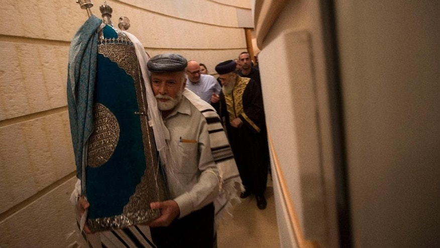 Israeli Foreign Ministry worker Yitshak Ozeri carries an ancient Torah scroll during a dedication ceremony at the Israeli Foreign Ministry in Jerusalem, Thursday, Jan. 22, 2015. The scroll that Israeli experts said was written 200 years ago has taken an unusual and mysterious journey from Baghdad to Jerusalem where it was greeted with candies and song in the jubilant dedication ceremony Thursday. (AP Photo/Sebastian Scheiner)