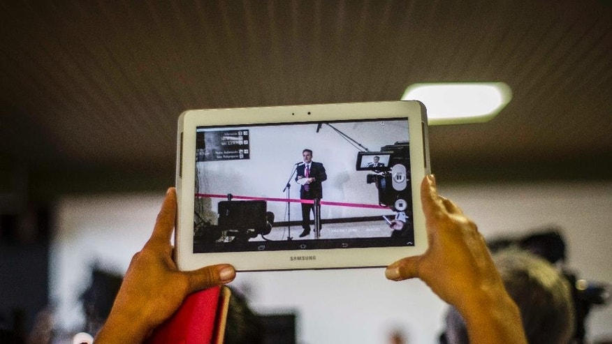 A journalist records a video with a tablet of Gustavo Machin, Cuba's deputy chief of North American affairs, during the second day of talks between Cuban and U.S. officials, in Havana, Cuba, Thursday, Jan. 22, 2015. The United States and Cuba are trying to eliminate obstacles to normalized ties as the highest-level U.S. delegation to the communist island in more than three decades holds a second day of talks with Cuban officials. (AP Photo/Ramon Espinosa)