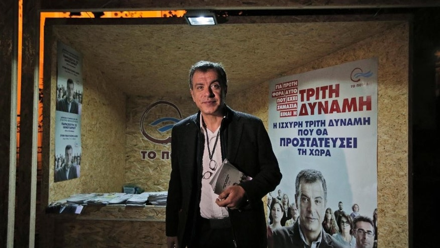 This photo taken on Wednesday, Jan. 21, 2015 shows Stavros Theodorakis, 51, leader of the political party To Potami (The River) poses for the photographers in front of a kiosk of his party central Athens. Greece goes to the polls on Sunday, Jan. 25, 2015 in a snap general election as the country was showing tentative signs of emerging from a deep financial crisis that has disturbed the eurozone. The vote, held more than a year early, has once more raised the specter of Grexit _ a Greek exit from Europe's joint currency. The sign reads in Greek: ' Third power, the strong third power that will protect the country', referring to some poll results that suggest Potami could get the third place in the upcoming elections. (AP Photo/Lefteris Pitarakis)