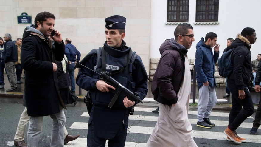 Jan. 9, 2015 - FILE photo of a French police officer standing guard outside the Grand Mosque as people arrive for Friday prayers in Paris. At least as many anti-Muslim acts have taken place in France since the terror attacks this month as for all of last year, a leading Muslim group reported Friday.