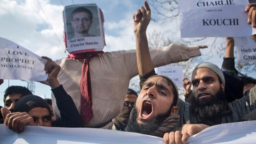 Kashmiri Muslims shout anti-French and pro-religious slogans during a protest in Srinagar, India, Friday, Jan. 23, 2015. Businesses and shops closed Friday in Indian-held Kashmir in a strike called by separatists and religious parties protesting the publication of a caricature of Prophet Muhammad in the latest issue of French satirical weekly Charlie Hebdo. (AP Photo/Dar Yasin)