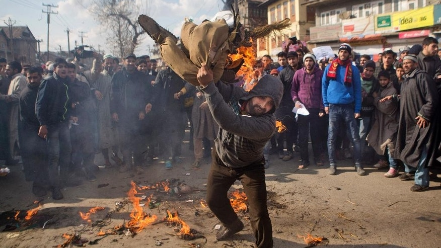 A Kashmiri Muslim man beats the burning effigy representing the French magazine Charlie Hebdo during a protest in Srinagar, India, Friday, Jan. 23, 2015. Businesses and shops closed Friday in Indian-held Kashmir in a strike called by separatists and religious parties protesting the publication of a caricature of Prophet Muhammad in the latest issue of French satirical weekly Charlie Hebdo. (AP Photo/Dar Yasin)