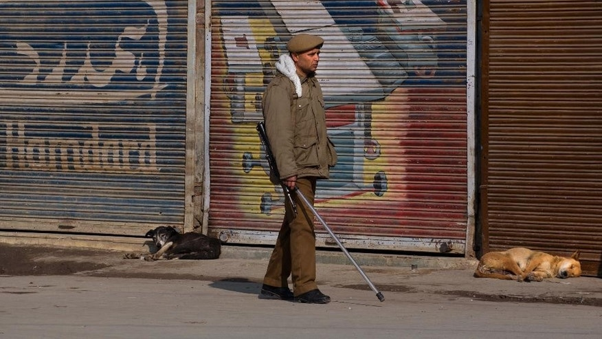 An Indian policeman stands guard outside a closed market during a strike against caricatures published in French magazine Charlie Hebdo, in Srinagar, India, Friday, Jan. 23, 2015. Businesses and shops have closed in Indian-held Kashmir in a daylong strike called by separatists and religious parties protesting the publication of a caricature of Prophet Muhammad in the latest issue of French satirical weekly Charlie Hebdo.(AP Photo/ Dar Yasin)