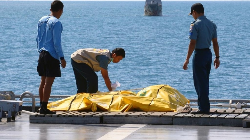 Jan. 23, 2015 - Crew members inspect bags containing bodies believed to be victims of   Flight 8501 on the deck of Indonesian Navy ship on the Java Sea, Indonesia. For the 1st time, Indonesian divers entered the fuselage of the AirAsia jetliner that crashed last month, and retrieved 6 bodies, an official said.