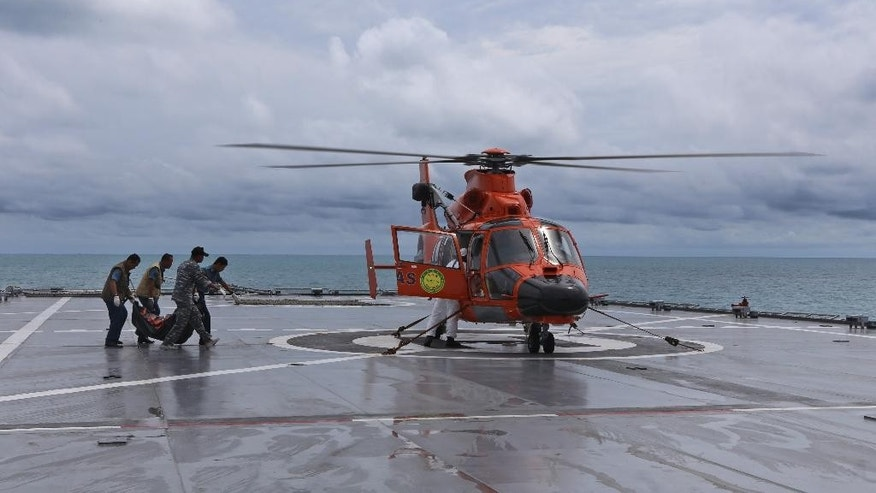 Military personnel load a bodybag containing what is believed to be a victim of AirAsia QZ 8501 onto a helicopter on the deck of Indonesian Navy ship KRI Banda Aceh in the Java Sea, Indonesia, Thursday, Jan. 22, 2015. Indonesian divers retrieved Thursday six more bodies from waters around the sunken fuselage of the AirAsia jetliner that crashed last month. (AP Photo/Natanael Pohan)
