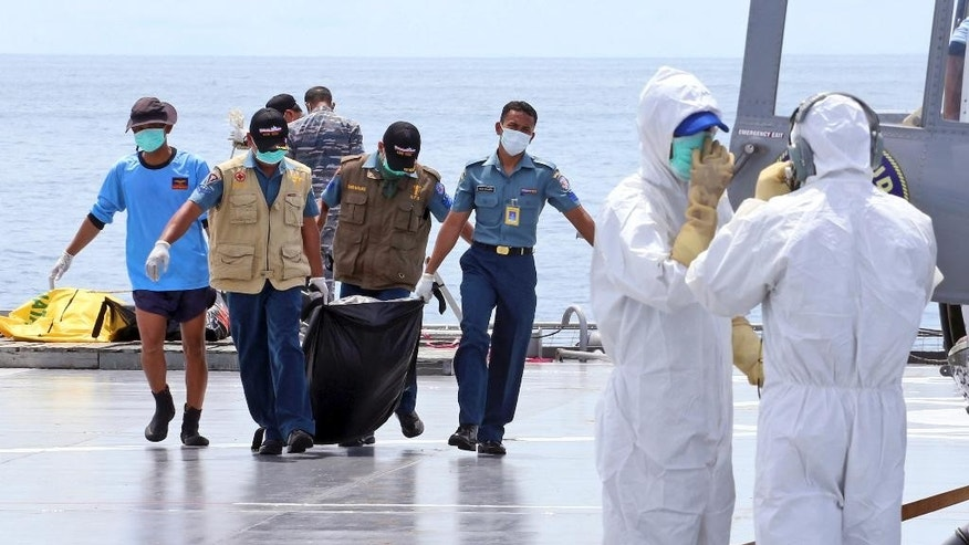 Crew members carry a bag containing the body believed to be a victim of AirAsia Flight 8501 to a waiting helicopter on the deck of Indonesian Navy ship KRI Banda Aceh, on the Java Sea, Indonesia, Friday, Jan. 23, 2015. The ill-fated jetliner plunged into the Java Sea while en route from Surabaya, Indonesia's second-largest city, to Singapore last month. (AP Photo/Natanael Pohan)
