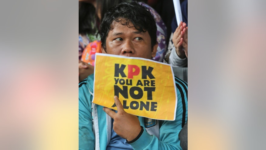 A supporter of the Indonesian Corruption Eradication Commission (KPK) holds a poster during a protest against the arrest of the deputy head of the Corruption Eradication Commission Bambang Widjojanto by the police, outside the commission's office in Jakarta, Indonesia, Friday, Jan. 23, 2015. Widjojanto was arrested Friday, days after he said a national police chief hopeful was a graft suspect, sparking public demands for the country's president to defend the body. (AP Photo/Tatan Syuflana)